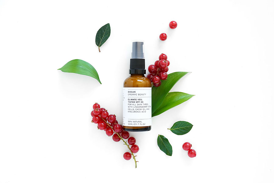 Evolve Beauty natural beauty product called Climate Veil in a bottle surrounded by leaves and berries